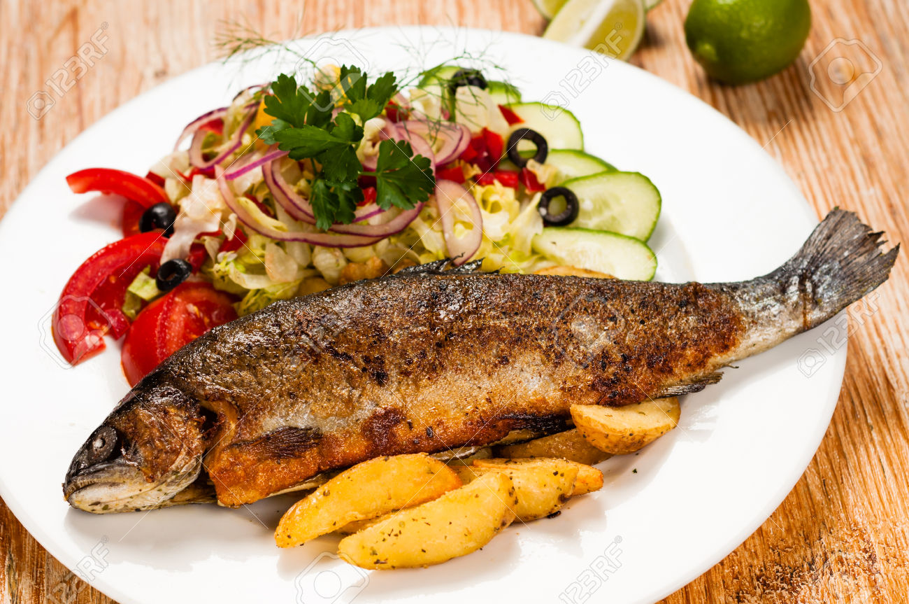 Fried trout and potato wedges on wooden table